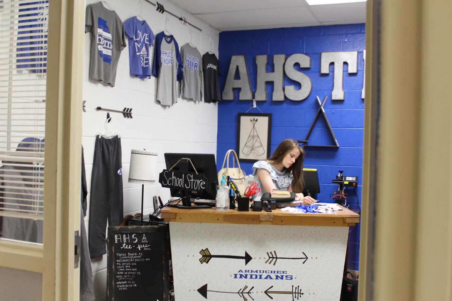 This photo has captured a student intern working in the TeePee store. It displays the merchandise we have to pick from and the prices that they cost. With the blue paint on the walls and the school colors all over the room, the TeePee store radiates school spirit.