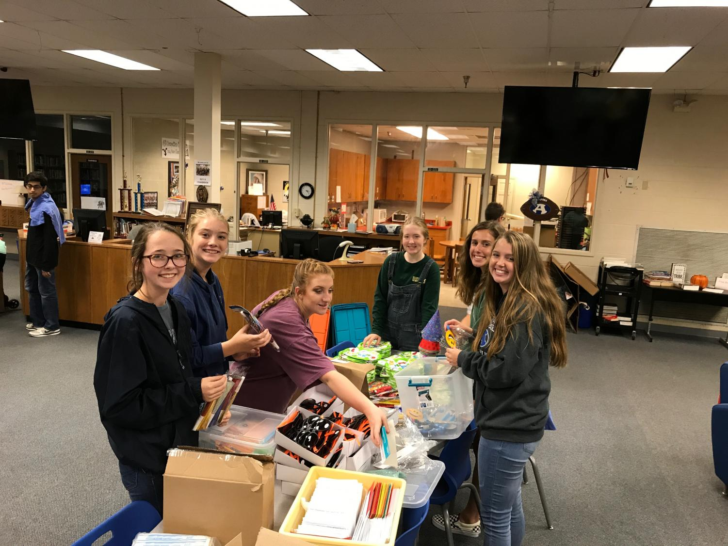 A group of Key Club members stops working for a moment to pose for a photo before resuming putting the bags together. At this table they will pack sun glasses, crayons, and all other manner of fun items into the bag.