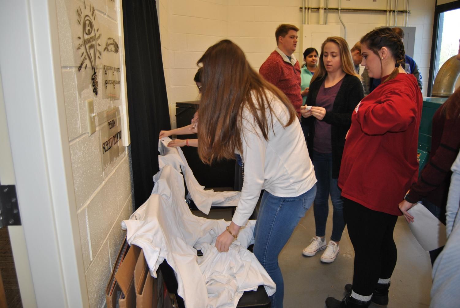 Students+Ally+O%27Neal%2C+Olivia+Crumbly%2C+and+Story+Hubbard+are+helping+fellow+students+by+folding+the+finished+t-shirts.