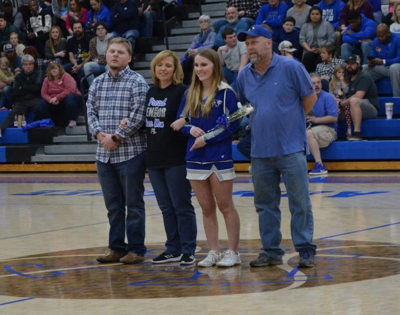 Senior, Maura Duke stands with her family after being represented on senior night.