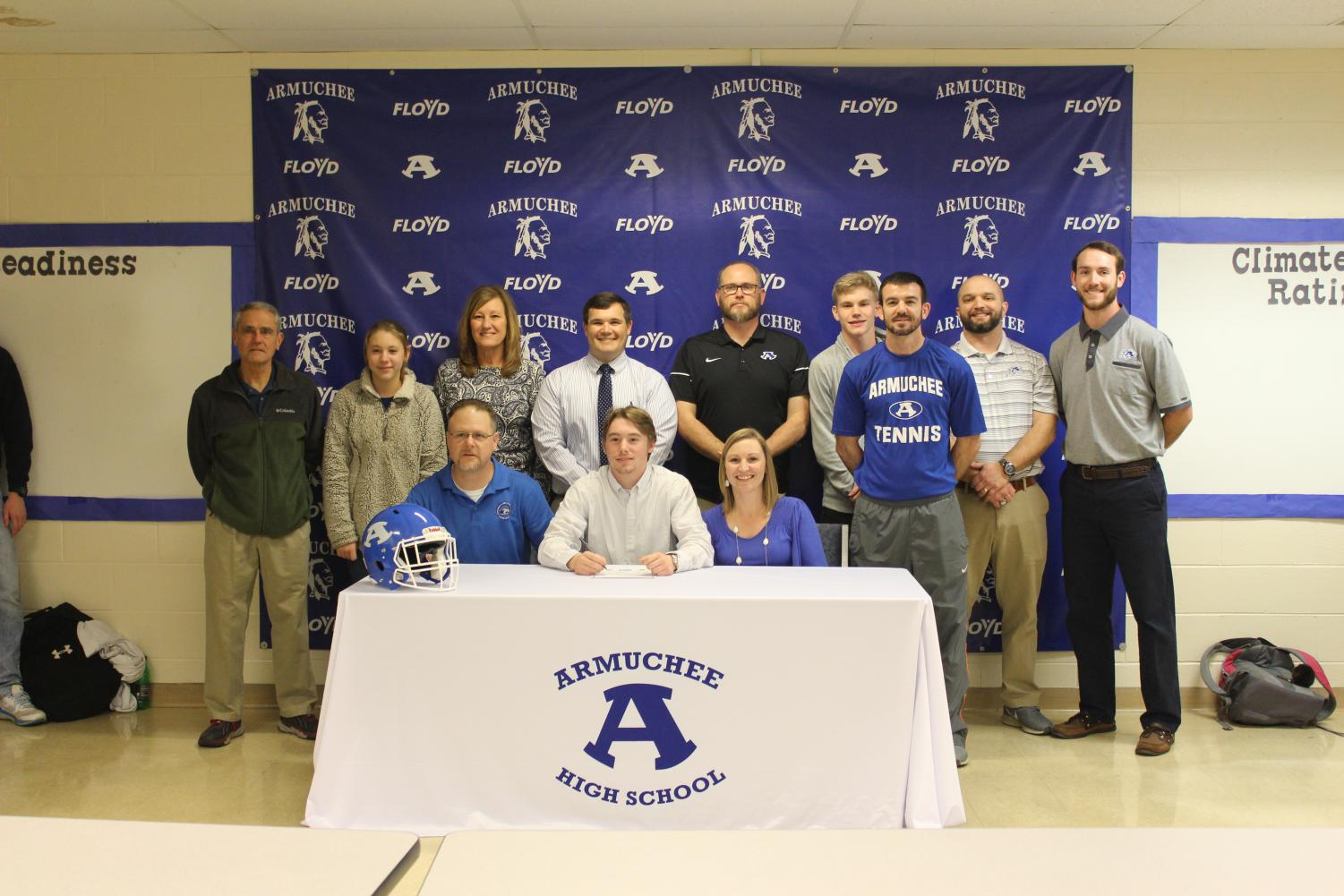 Brayden Butler signs with his family, coaching, and administrative staff supporting him.