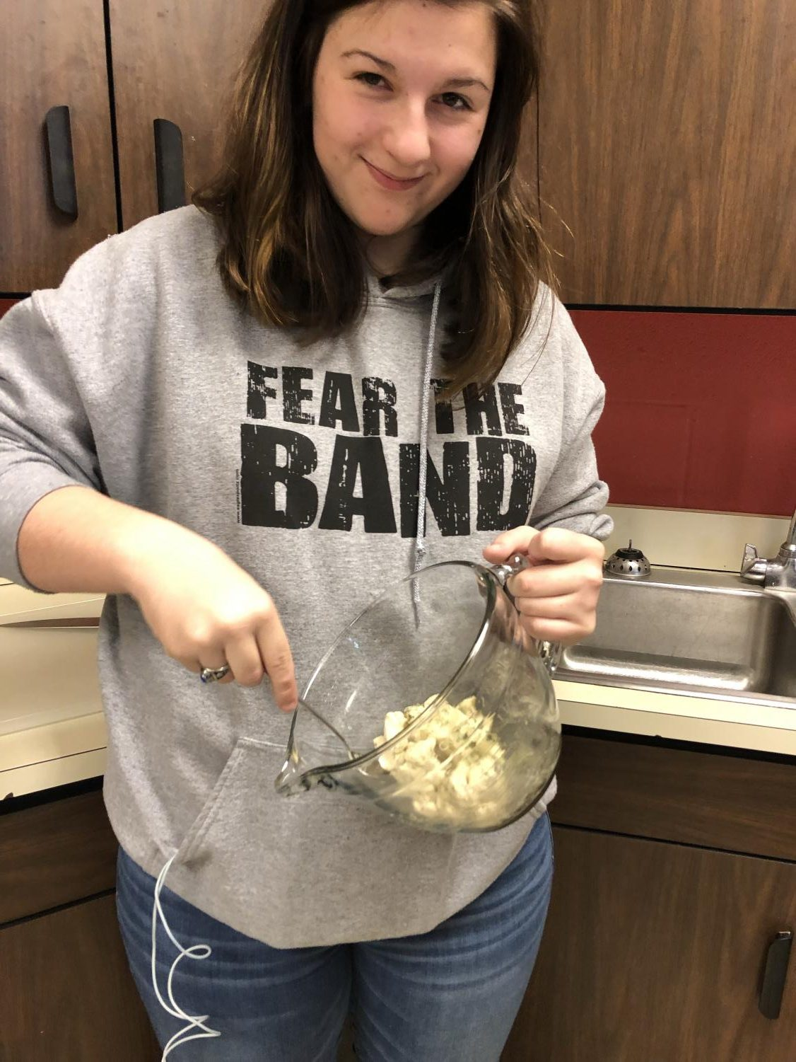 In this photo, junior Victoria Merrit is also following the recipe and is mixing the dough with the butter and dill mixture.