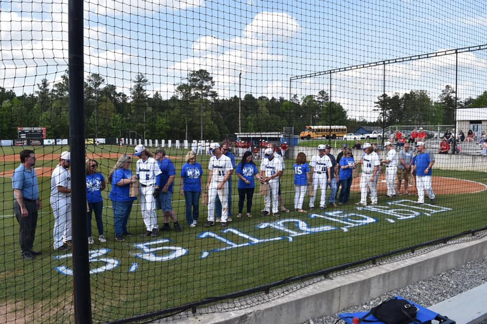 Senior+baseball+players+standing+with+their+parents+on+senior+night.+